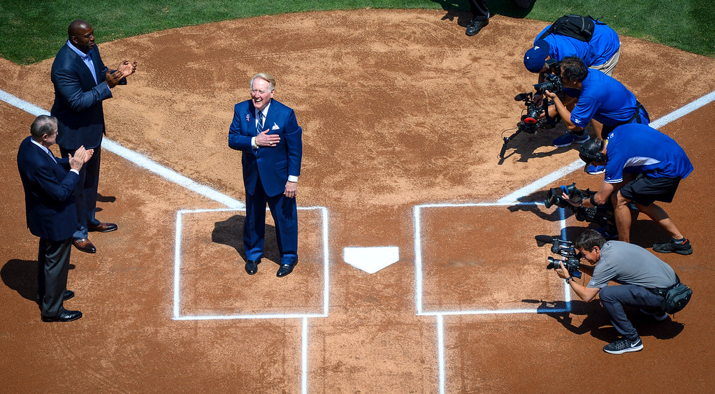 . The voice of the Dodgers, Vin Scully, places his hand over his heart as the crowd cheers before he received the opening pitch for the home opener at Dodger stadium Tuesday, April 12, 2016.   At left are former Dodger owner Peter O\'Malley and current owner Magic Johnson.  (Photo by David Crane Southern California News Group)