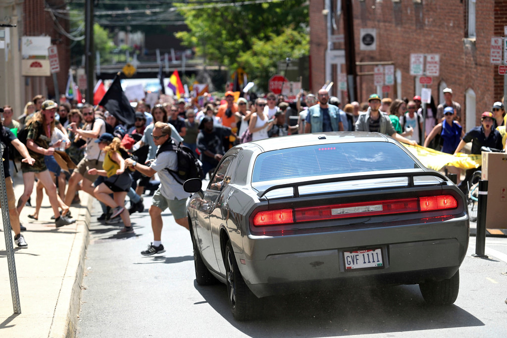 . A vehicle drives into a group of protesters demonstrating against a white nationalist rally in Charlottesville, Va., Saturday, Aug. 12, 2017. The nationalists were holding the rally to protest plans by the city of Charlottesville to remove a statue of Confederate Gen. Robert E. Lee. There were several hundred protesters marching in a long line when the car drove into a group of them.   /The Daily Progress via AP)