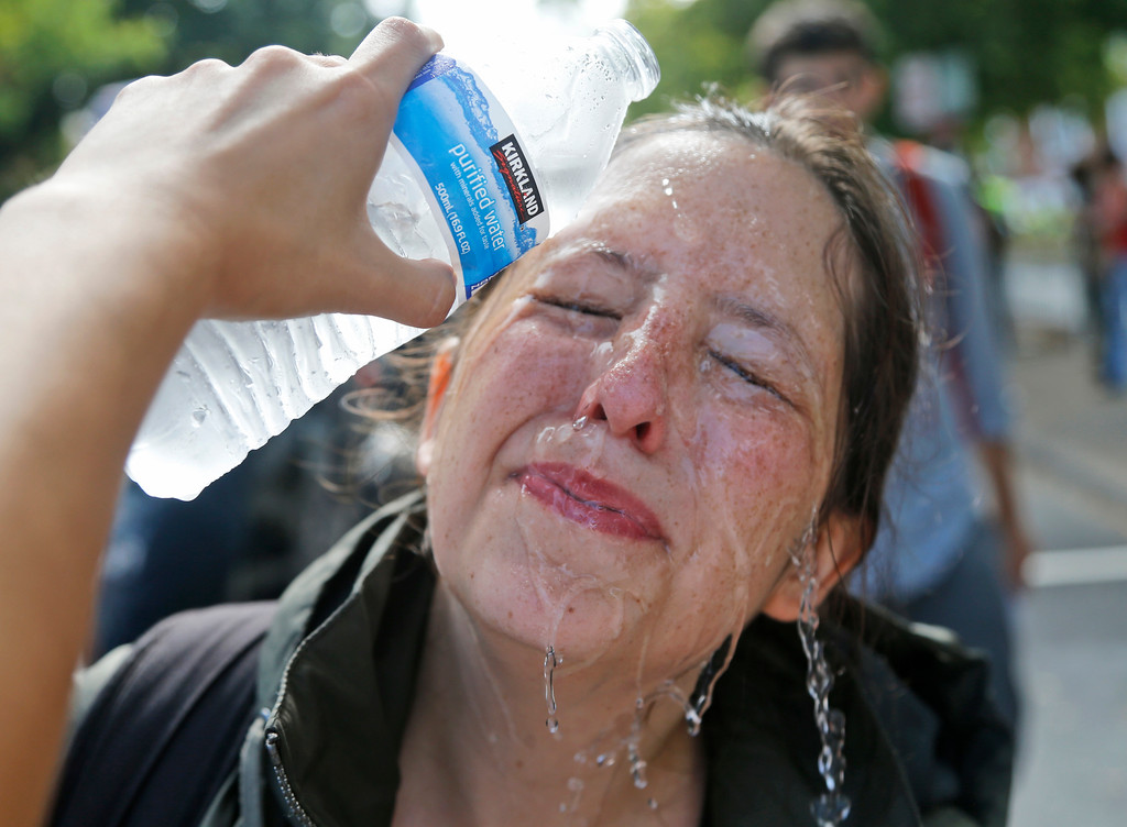 . A counter demonstrator gets a splash of water after being hit by pepper spray at the entrance to Lee Park in Charlottesville, Va., Saturday, Aug. 12, 2017. Gov. Terry McAuliffe declared a state of emergency and police dressed in riot gear ordered people to disperse after chaotic violent clashes between white nationalists and counter protestors. (AP Photo/Steve Helber)