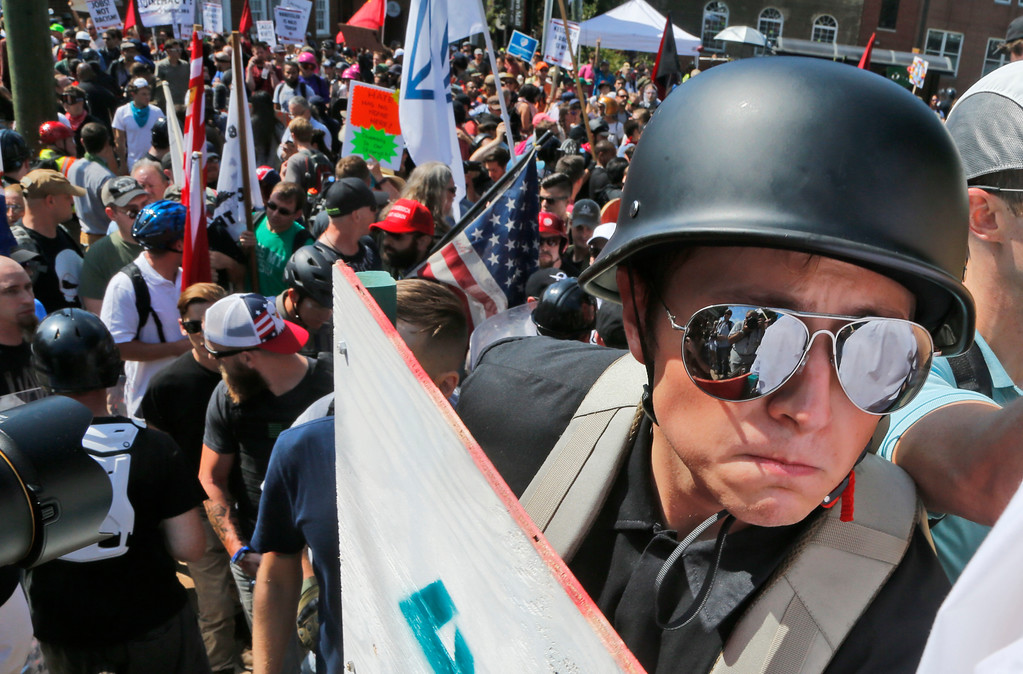 . A white nationalist demonstrator with a helmet and shield walks into Lee Park in Charlottesville, Va., Saturday, Aug. 12, 2017.   Hundreds of people chanted, threw punches, hurled water bottles and unleashed chemical sprays on each other Saturday after violence erupted at a white nationalist rally in Virginia. At least one person was arrested.  (AP Photo/Steve Helber)