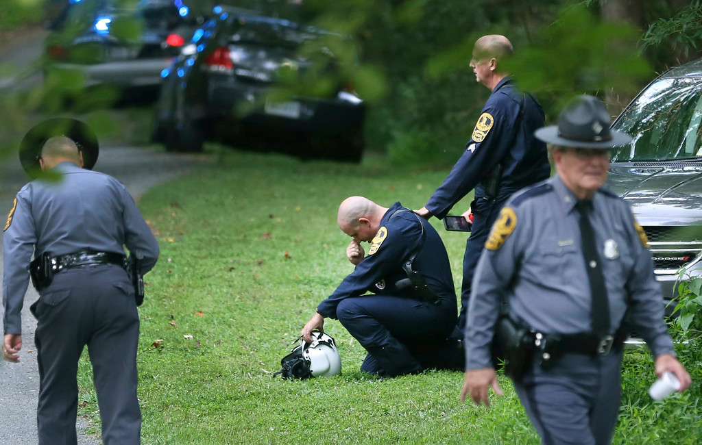 . Authorities work near the scene of a deadly helicopter crash near Charlottesville, Va., on Saturday Aug. 12, 2017. (Shelby Lum/Richmond Times-Dispatch via AP)