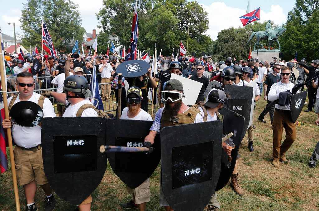 . White nationalist demonstrators hold their ground as they clash with counter demonstrators in Lee Park in Charlottesville, Va., Saturday, Aug. 12, 2017.  Hundreds of people chanted, threw punches, hurled water bottles and unleashed chemical sprays on each other Saturday after violence erupted at a white nationalist rally in Virginia. At least one person was arrested.  (AP Photo/Steve Helber)