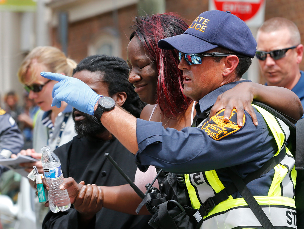 . Rescue personnel help an injured woman after a car ran into a large group of protesters after an white nationalist rally in Charlottesville, Va., Saturday, Aug. 12, 2017.  The nationalists were holding the rally to protest plans by the city of Charlottesville to remove a statue of Confederate Gen. Robert E. Lee. There were several hundred protesters marching in a long line when the car drove into a group of them. (AP Photo/Steve Helber)