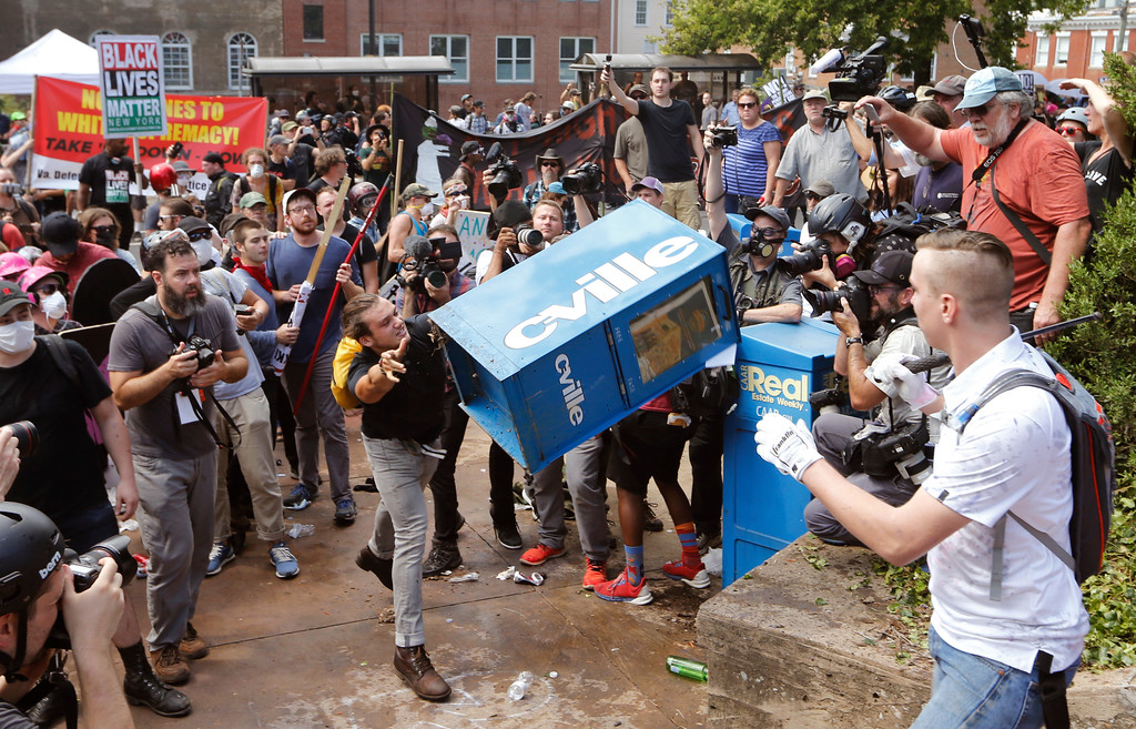 . White nationalist demonstrators clash with a counter demonstrator  as he throws a newspaper box at the entrance to Lee Park in Charlottesville, Va., Saturday, Aug. 12, 2017. Gov. Terry McAuliffe declared a state of emergency and police dressed in riot gear ordered people to disperse after chaotic violent clashes between white nationalists and counter protestors. (AP Photo/Steve Helber) (AP Photo/Steve Helber)