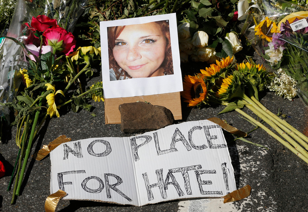 . A makeshift memorial of flowers and a photo of victim, Heather Heyer, sits in Charlottesville, Va., Sunday, Aug. 13, 2017. Heyer died when a car rammed into a group of people who were protesting the presence of white supremacists who had gathered in the city for a rally. (AP Photo/Steve Helber)