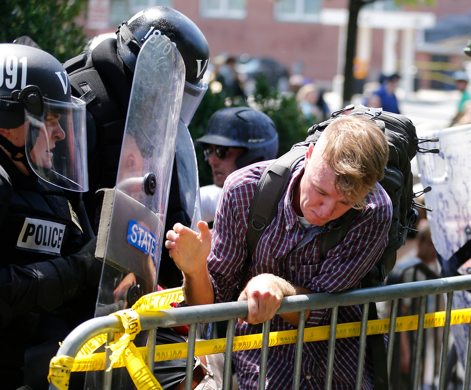 . An white nationalist demonstrator is pushed out of the park by police at the entrance to Lee Park in Charlottesville, Va., Saturday, Aug. 12, 2017.  Gov. Terry McAuliffe declared a state of emergency and police dressed in riot gear ordered people to disperse after chaotic violent clashes between white nationalists and counter protestors. (AP Photo/Steve Helber)