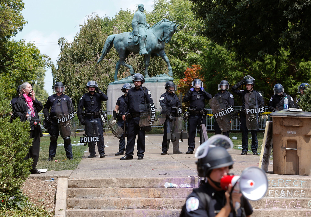 . State Police in riot gear guard Lee Park after a white nationalist demonstration was declared illegal and the park was cleared in Charlottesville, Va., Saturday, Aug. 12, 2017.  Hundreds of people chanted, threw punches, hurled water bottles and unleashed chemical sprays on each other Saturday after violence erupted at the white nationalist rally. (AP Photo/Steve Helber)