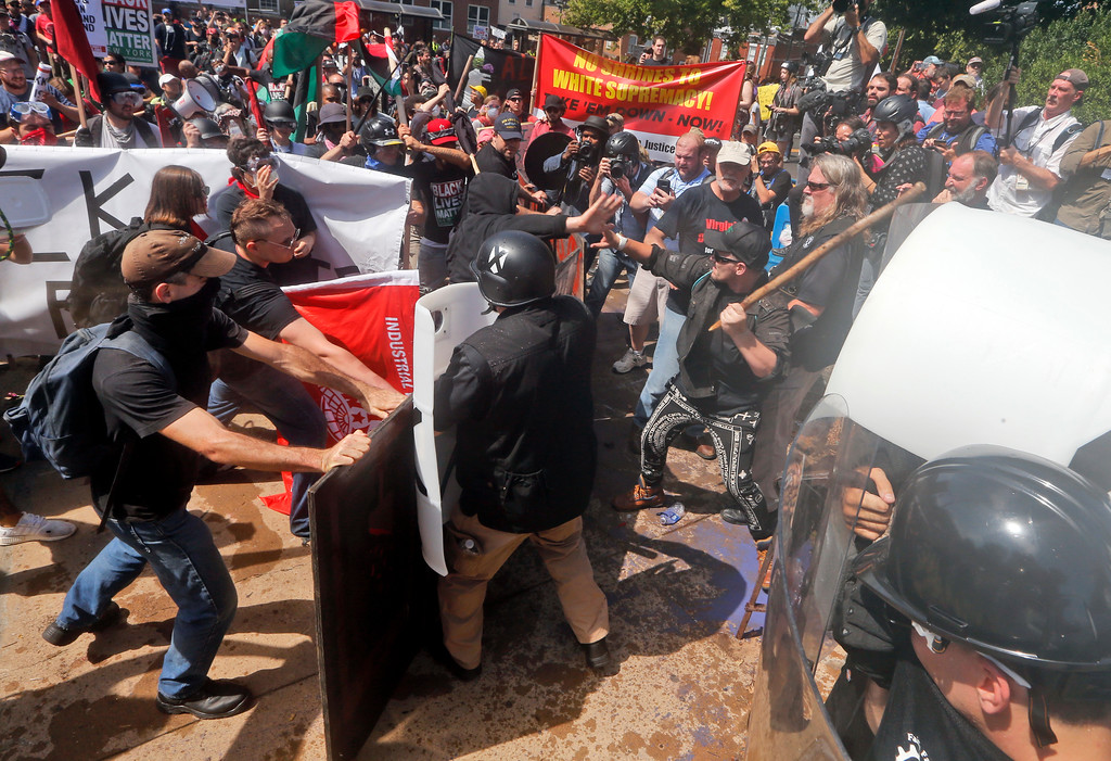 . White nationalist demonstrators clash with counter demonstrators at the entrance to Lee Park in Charlottesville, Va., Saturday, Aug. 12, 2017. Gov. Terry McAuliffe declared a state of emergency and police dressed in riot gear ordered people to disperse after chaotic violent clashes between white nationalists and counter protestors. (AP Photo/Steve Helber)
