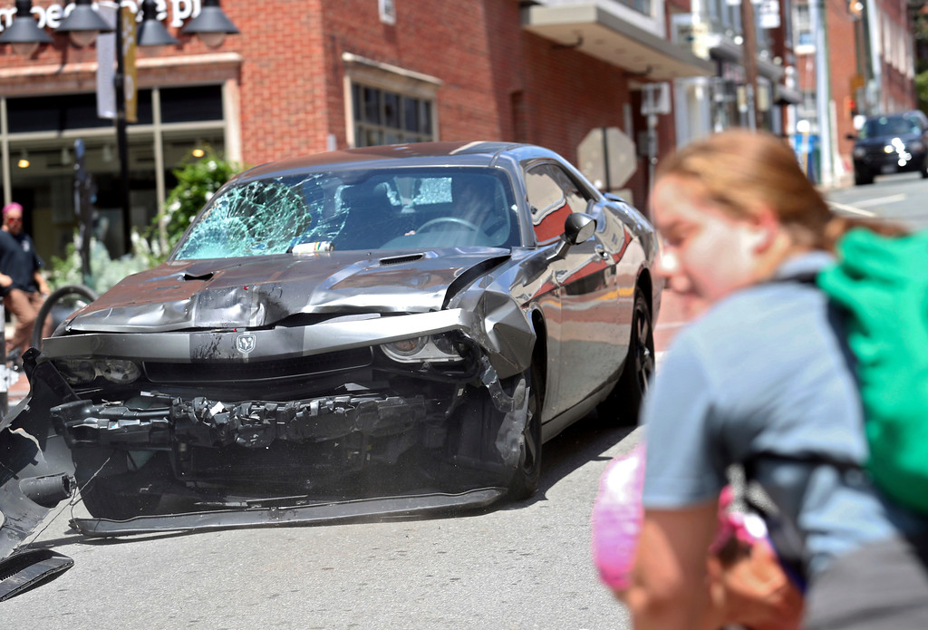 . A vehicle reverses after driving into a group of protesters demonstrating against a white nationalist rally in Charlottesville, Va., Saturday, Aug. 12, 2017. The nationalists were holding the rally to protest plans by the city of Charlottesville to remove a statue of Confederate Gen. Robert E. Lee. There were several hundred protesters marching in a long line when the car drove into a group of them. (Ryan M. Kelly/The Daily Progress via AP)