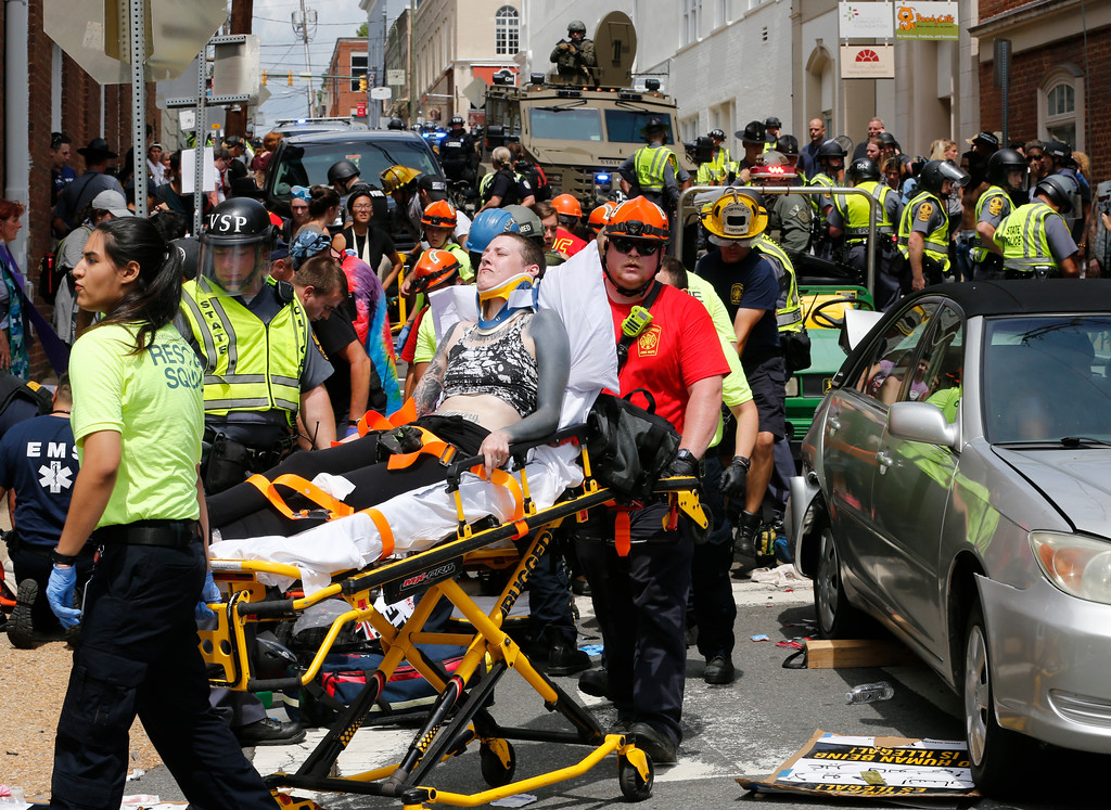 . Rescue personnel help injured people after a car ran into a large group of protesters after a white nationalist rally in Charlottesville, Va., Saturday, Aug. 12, 2017. The nationalists were holding the rally to protest plans by the city of Charlottesville to remove a statue of Confederate Gen. Robert E. Lee. There were several hundred protesters marching in a long line when the car drove into a group of them. (AP Photo/Steve Helber)