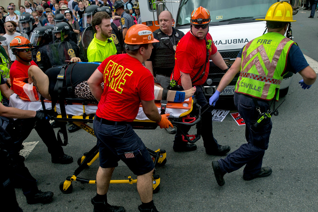 . An injured person is taken away by Emergency Medical Services workers after a car ran into pedestrians during a white nationalist rally, Saturday Aug. 12, 2017, in Charlottesville, Va. (Shaban Athuman/Richmond Times-Dispatch via AP)