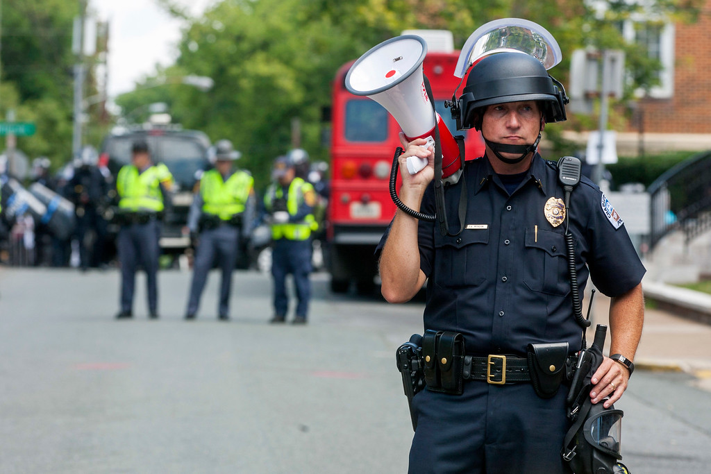. A police officer stands in the middle of the street after declaring the protest an unlawful assembly during a white nationalist rally, on Saturday Aug. 12, 2017, in Charlottesville, Va. (Shaban Athuman/Richmond Times-Dispatch via AP)