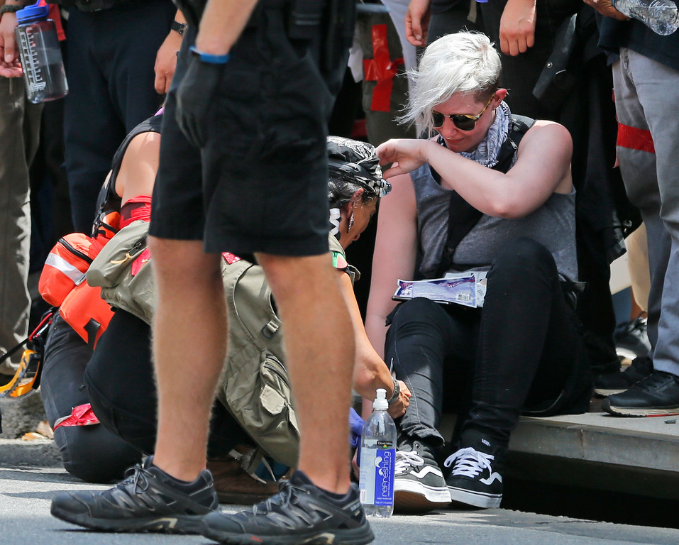. Rescue personnel help injured people after a car ran into a large group of protesters after an white nationalist rally in Charlottesville, Va., Saturday, Aug. 12, 2017. The nationalists were holding the rally to protest plans by the city of Charlottesville to remove a statue of Confederate Gen. Robert E. Lee. There were several hundred protesters marching in a long line when the car drove into a group of them.  (AP Photo/Steve Helber)
