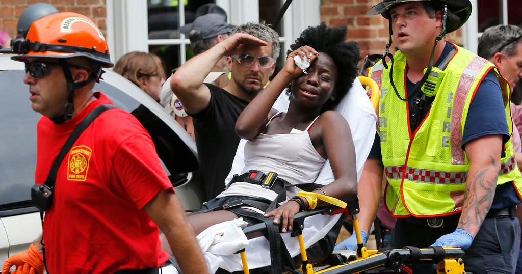 . Rescue personnel help an injured woman after a car ran into a large group of protesters after an white nationalist rally in Charlottesville, Va., Saturday, Aug. 12, 2017.  The nationalists were holding the rally to protest plans by the city of Charlottesville to remove a statue of Confederate Gen. Robert E. Lee. There were several hundred protesters marching in a long line when the car drove into a group of them.(AP Photo/Steve Helber)