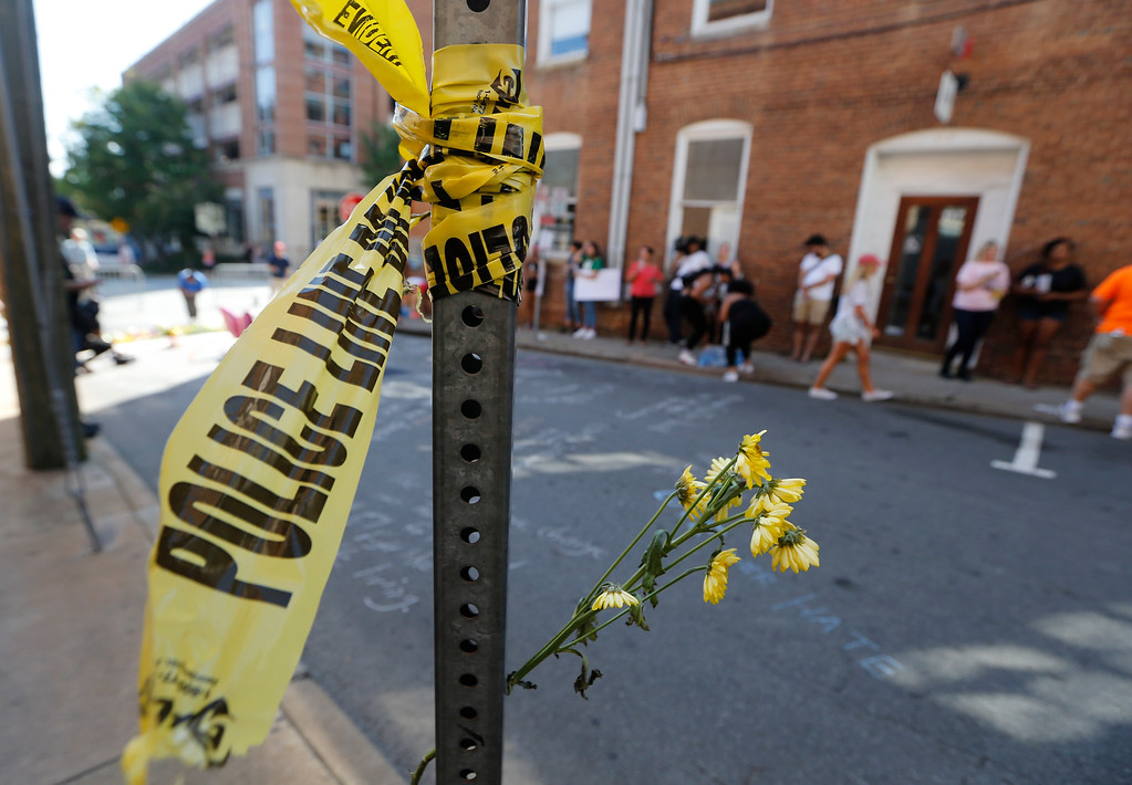 . Police tape and flowers mark the spot of a car attack after a Alt Right rally and violence that killed Heather Heyer in Charlottesville, Va., Sunday, Aug. 13, 2017. Heyer died when a car rammed into a group of people who were protesting the presence of white supremacists who had gathered in the city for a rally.  (AP Photo/Steve Helber)