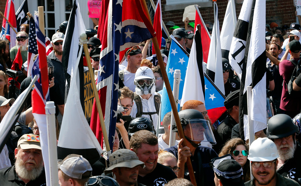 . White nationalist demonstrators walk into the entrance of Lee Park surrounded by counter demonstrators in Charlottesville, Va., Saturday, Aug. 12, 2017. Gov. Terry McAuliffe declared a state of emergency and police dressed in riot gear ordered people to disperse after chaotic violent clashes between white nationalists and counter protestors. (AP Photo/Steve Helber)