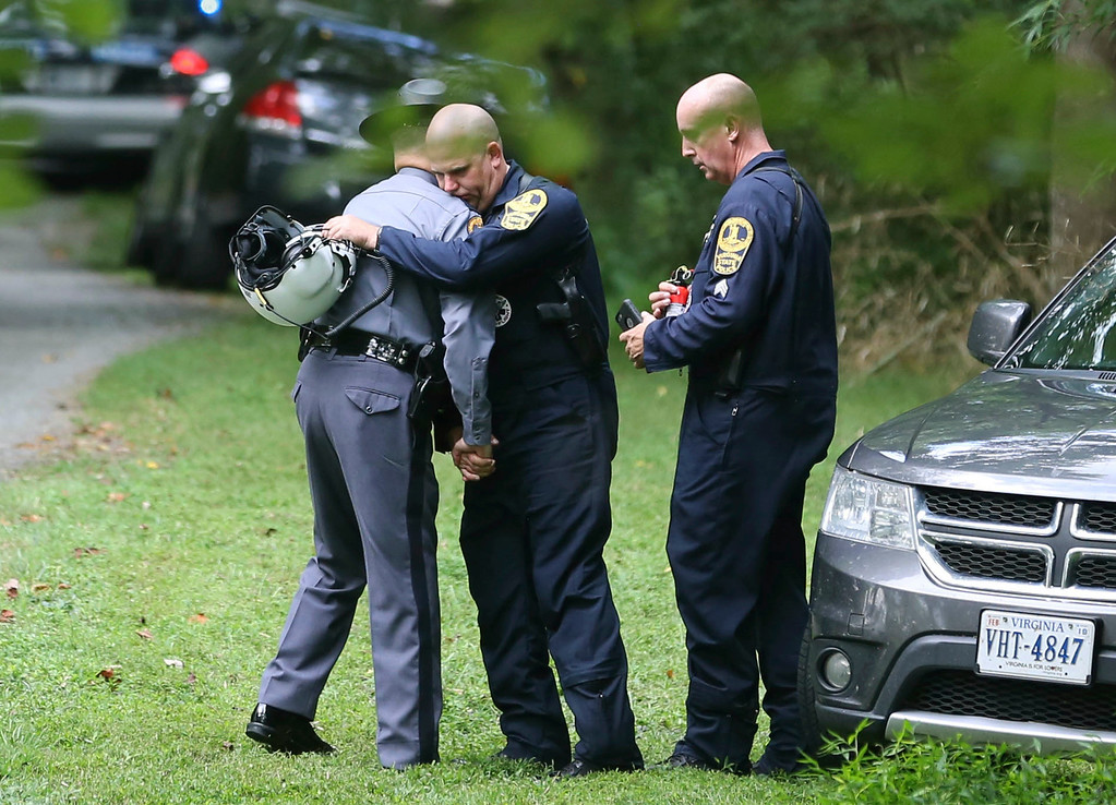 . Authorities embrace while working near the scene of a deadly helicopter crash near Charlottesville, Va., on Saturday Aug. 12, 2017. (Shelby Lum/Richmond Times-Dispatch via AP)
