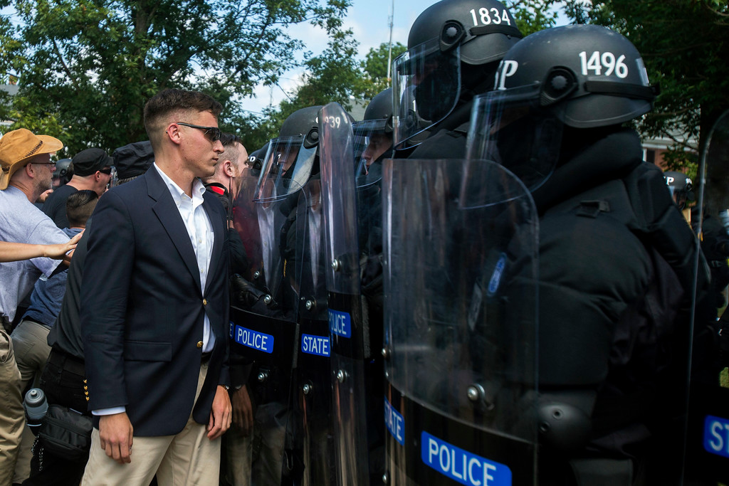 . A protester stands in front of  state troopers during a white nationalist rally on Saturday Aug. 12, 2017, in Charlottesville, Va. The group had gathered to protest plans by the city of Charlottesville to remove a statue of Confederate Gen. Robert E. Lee. (Shaban Athuman /Richmond Times-Dispatch via AP)