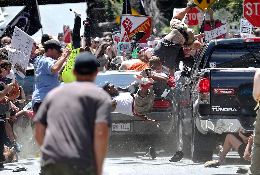 . People fly into the air as a vehicle drives into a group of protesters demonstrating against a white nationalist rally in Charlottesville, Va., Saturday, Aug. 12, 2017. The nationalists were holding the rally to protest plans by the city of Charlottesville to remove a statue of Confederate Gen. Robert E. Lee. There were several hundred protesters marching in a long line when the car drove into a group of them. (Ryan M. Kelly/The Daily Progress via AP)
