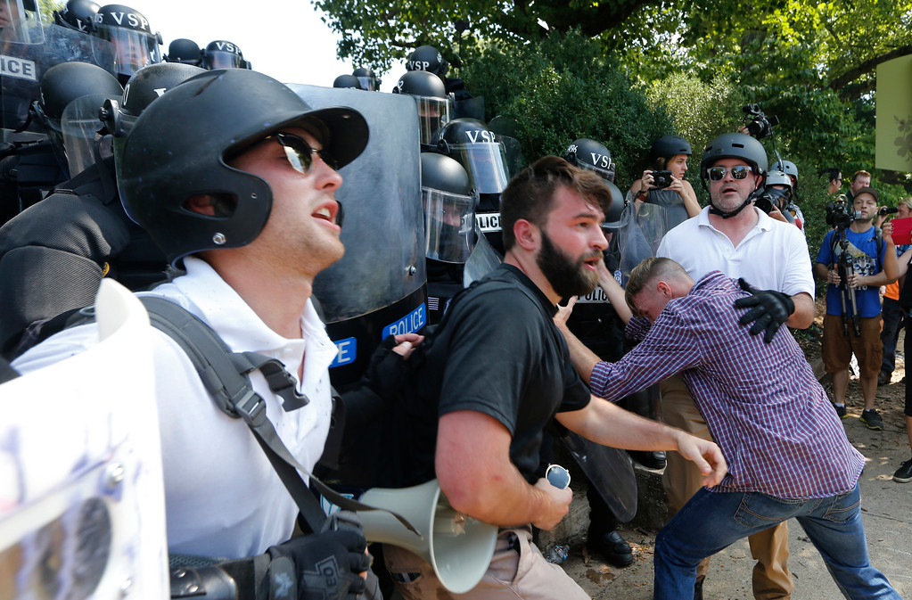 . White nationalist demonstrators clash with police at the entrance to Lee Park in Charlottesville, Va., Saturday, Aug. 12, 2017.  Gov. Terry McAuliffe declared a state of emergency and police dressed in riot gear ordered people to disperse after chaotic violent clashes between white nationalists and counter protestors. (AP Photo/Steve Helber)