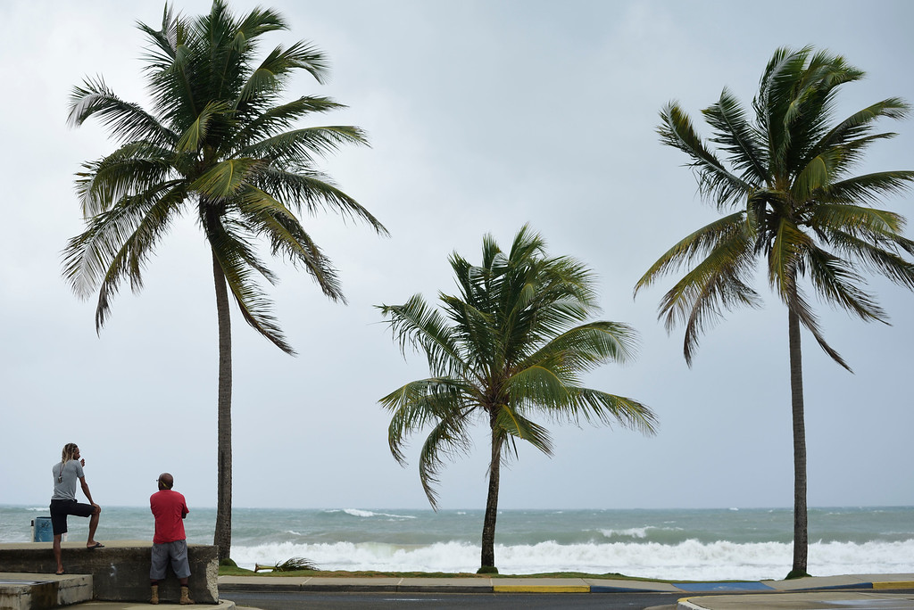 . People stand near the shore before the arrival of Hurricane Irma, in luquillo, Puerto Rico, Wednesday, Sept. 6, 2017. Irma roared into the Caribbean with record force early Wednesday, its 185-mph winds shaking homes and flooding buildings on a chain of small islands along a path toward Puerto Rico, Cuba and Hispaniola and a possible direct hit on densely populated South Florida. (AP Photo/Carlos Giusti)