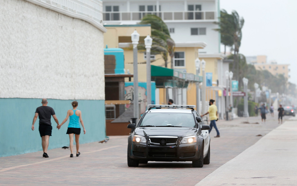 . A police cruiser with a loud speaker reminds beach goers along the Hollywood Beach Boardwalk that they only have a few minutes before the start of a curfew, Saturday, Sept. 9, 2017 in Fort Lauderdale, Fla. (AP Photo/Wilfredo Lee)
