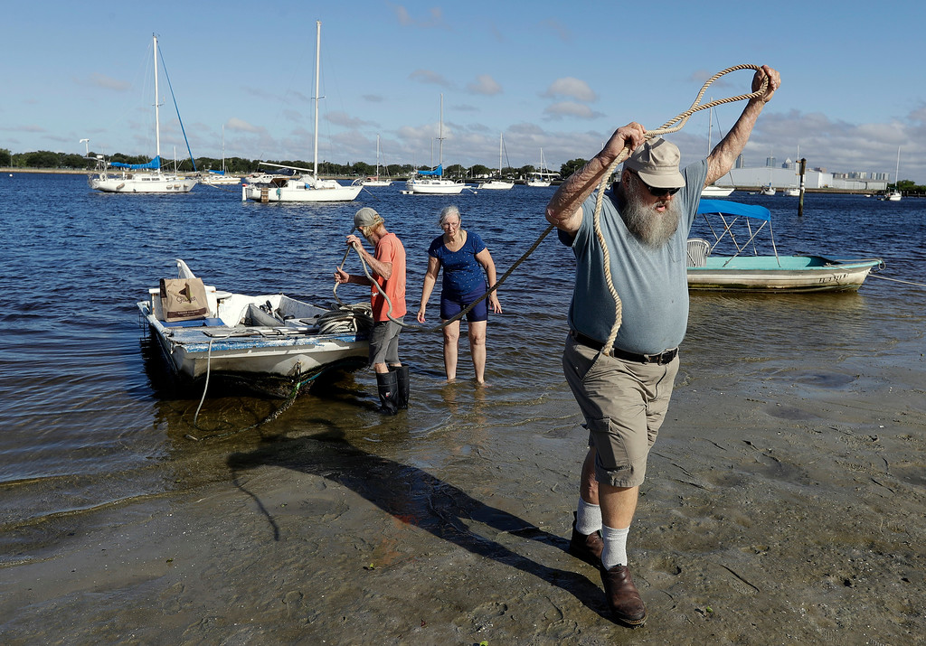 . Paul Barber, right, and Maudelene McCleary, center, help Red Grogg pull his boat out of the water along the Davis Islands yacht basin Saturday, Sept. 9, 2017, in Tampa, Fla. Residents along Florida\'s west coast are preparing for the arrival of Hurricane Irma. (AP Photo/Chris O\'Meara)