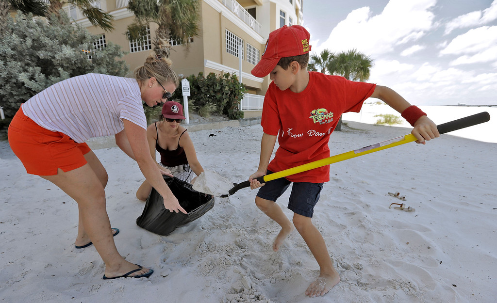 . Ramsey Abdelkader, right, helps Sherri Skala, left, and Jennifer Morales fill sand bags to help protect their restaurant Saturday, Sept. 9, 2017, in Clearwater Beach, Fla. Business and residents were under a mandatory evacuation order as Hurricane Irma continued to churn towards Florida. (AP Photo/Chris O\'Meara)