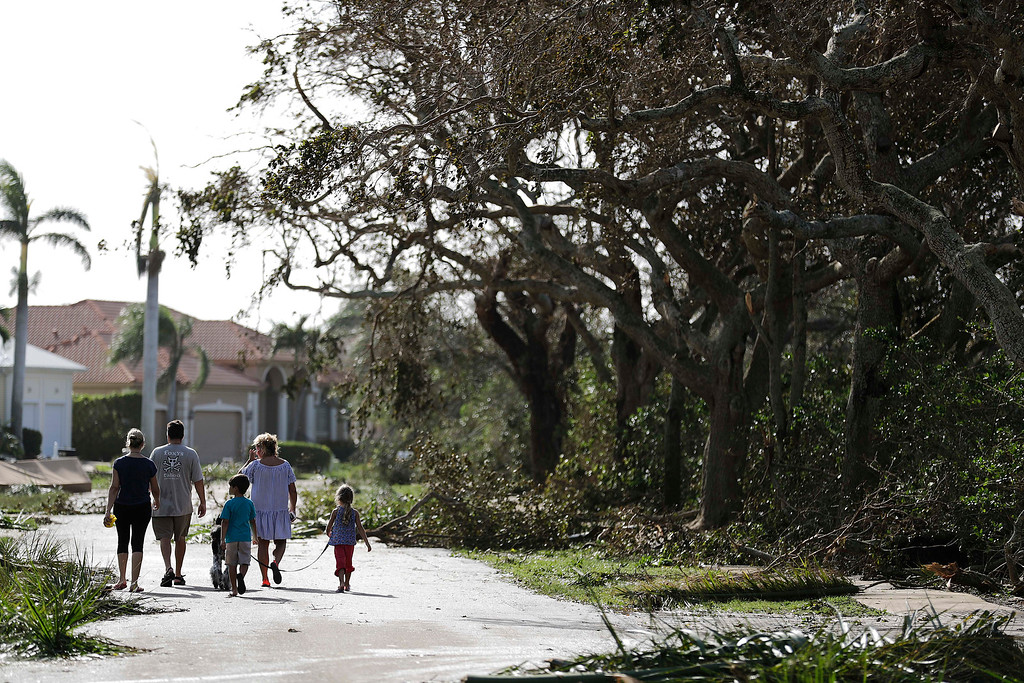 . A family walks through a street littered with fallen branches from Hurricane Irma in Marco Island, Fla., Monday, Sept. 11, 2017. (AP Photo/David Goldman)