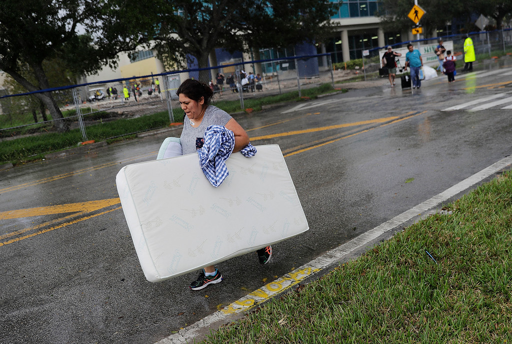 . Anna Leanaz carries her mattress as evacuees are moved to another building with more bathrooms while sheltering at Florida International University ahead of Hurricane Irma in Miami, Saturday, Sept. 9, 2017. (AP Photo/David Goldman)