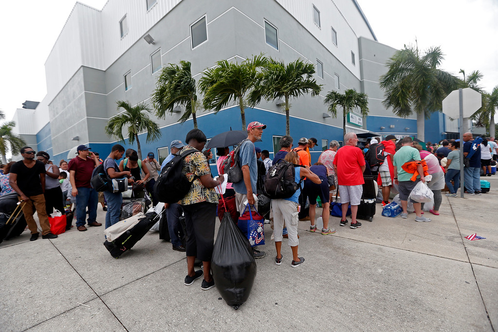 . Evacuees stand in line to enter the Germain Arena, which is being used as a fallout shelter, in advance of Hurricane Irma, in Estero, Fla., Saturday, Sept. 9, 2017. With the window closing fast for anyone wanting to escape, Irma hurtled toward Florida with 125 mph winds Saturday on a projected track that could take it away from Miami and instead give the Tampa area its first direct hit from a major hurricane in nearly a century. (AP Photo/Gerald Herbert)