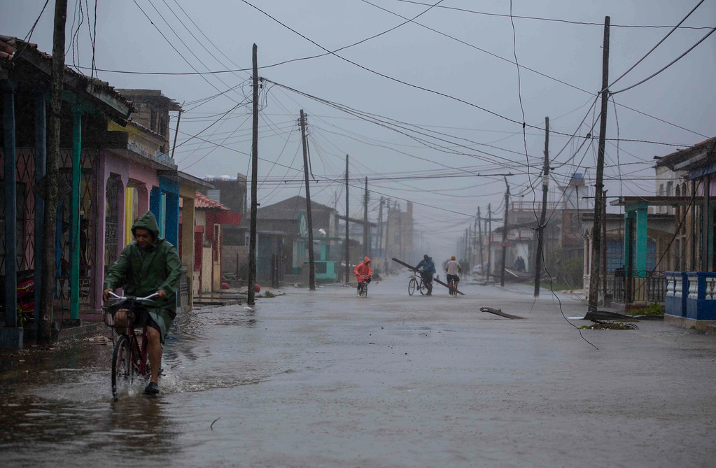 . Residents ride their bikes through flood waters in the aftermath of Hurricane Irma, in Caibarien, Cuba, Saturday, Sept. 9, 2017. There were no reports of deaths or injuries after heavy rain and winds from Irma lashed northeastern Cuba. Seawater surged three blocks inland in Caibarien. (AP Photo/Desmond Boylan)