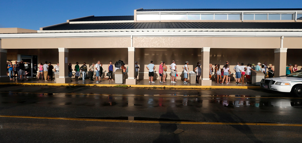 . People line up for the announced opening of a Publix grocery store, the first food chain to re-open in Naples, in the aftermath of Hurricane Irma, which passed through Sunday, in Naples, Fla., Tuesday, Sept. 12, 2017. The store could not open its doors on time because they were trying to get the cash registers online. (AP Photo/Gerald Herbert)