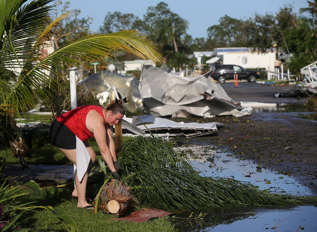 . Karyn Chapman cleans up debris in front of her destroyed home in the aftermath of Hurricane Irma in the Naples Estates mobile home park, in Naples, Fla., Tuesday, Sept. 12, 2017. (AP Photo/Gerald Herbert)
