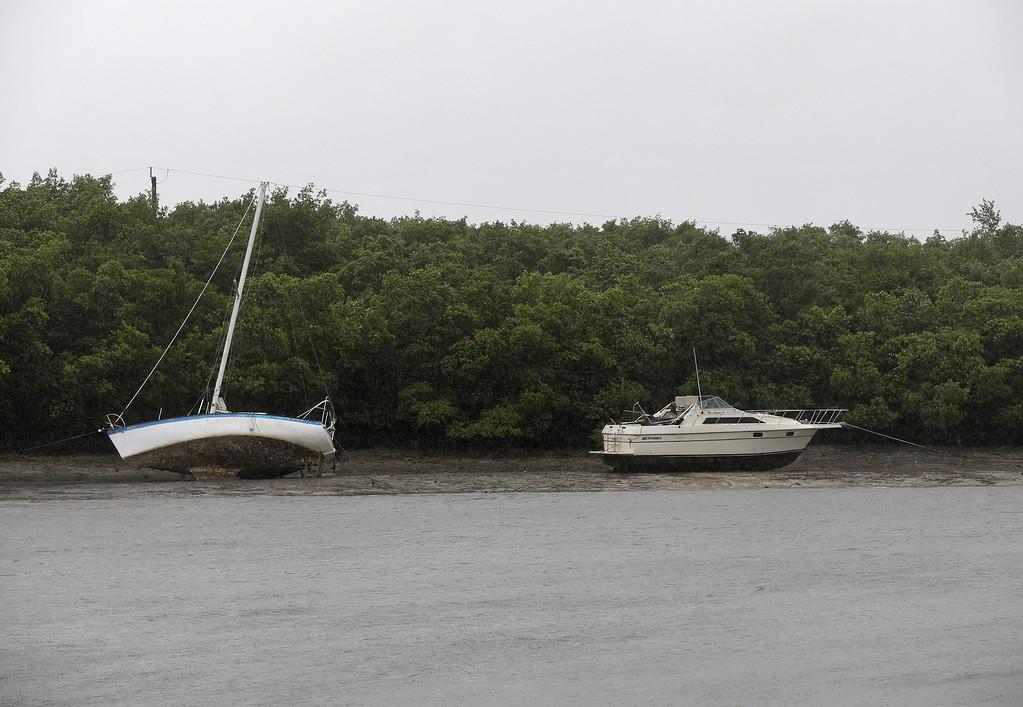 . Two boats that are moored sit in mud due to an unusually low tide, as the first effects of Hurricane Irma reach Fort Myers, Fla., Sunday, Sept. 10, 2017. Announcing itself with roaring 130 mph winds, Hurricane Irma plowed into the mostly emptied-out Florida Keys early Sunday. (AP Photo/Gerald Herbert)