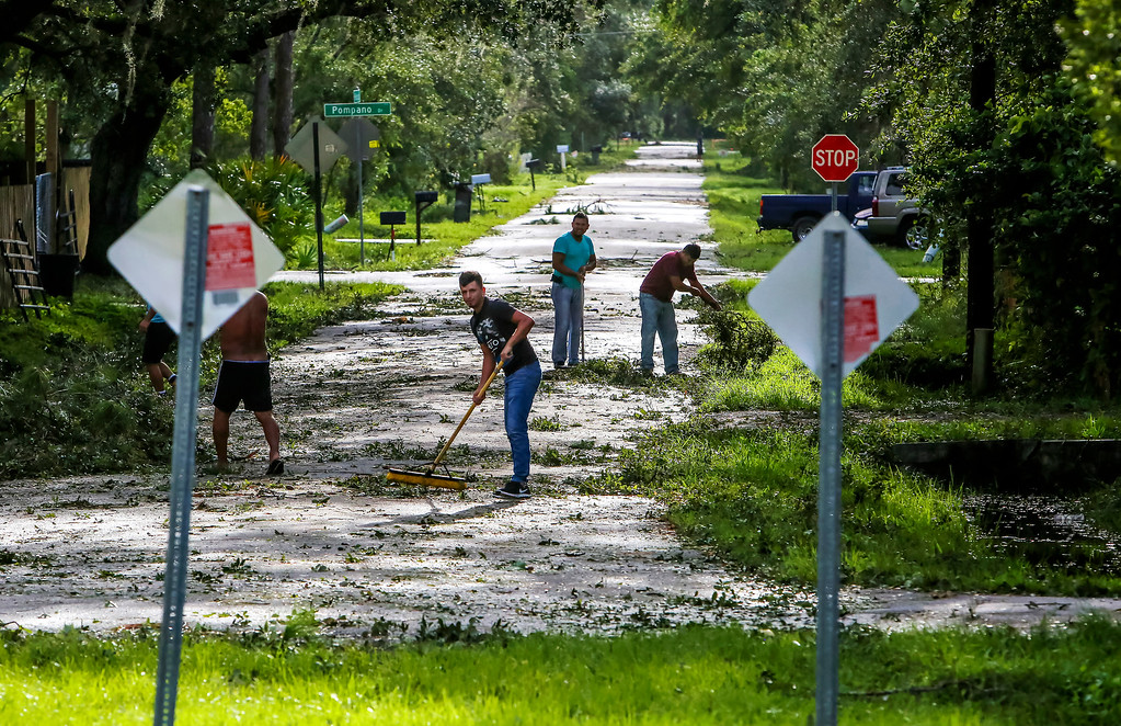 . Neighbors help each other clear their road of debris in Kissimmee, Fla., Monday, Sept. 11, 2017, as residents begin to clean up after Hurricane Irma plowed through the state. (Jacob Langston/Orlando Sentinel via AP)