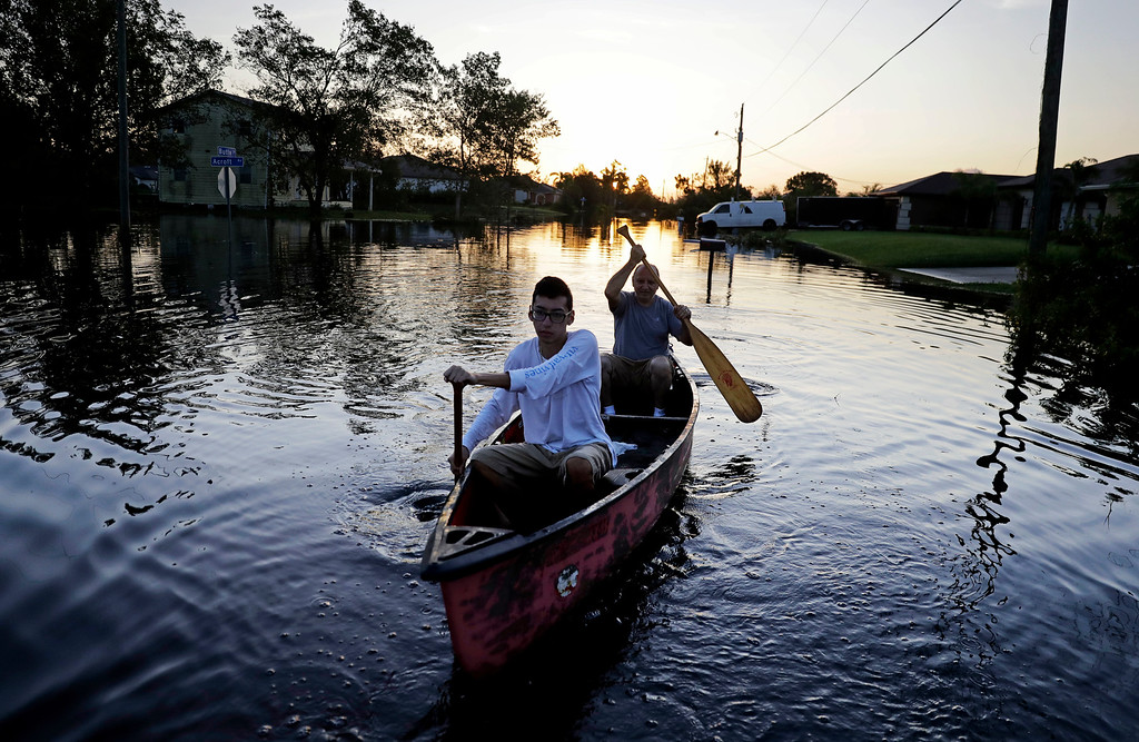 . Pierre Ghantos, rear, and his son Nathan paddle though their flooded neighborhood in the aftermath of Hurricane Irma in Fort Myers, Fla., Tuesday, Sept. 12, 2017. (AP Photo/David Goldman)