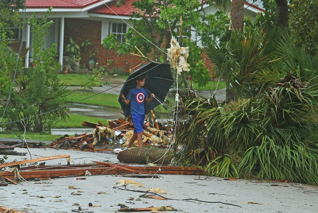 . Aden Alcroix-Camper, 11, walks through debris from a second- story roof scattered over 2 block area after a possible tornado touched down at Palm Bay Point subdivision in Palm Bay Fal., Sunday, Sept. 10, 2017, as Hurricane Irma made landfall in the state of Florida (Red Huber/Orlando Sentinel via AP)/Orlando Sentinel via AP)