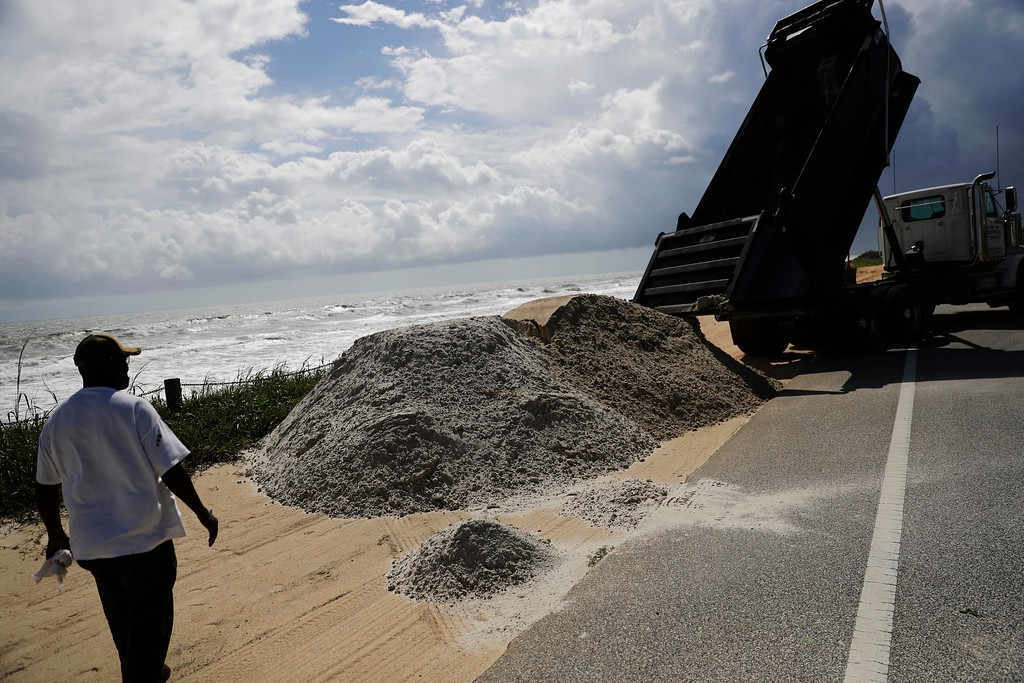 . Sand is dumped along the dunes on Route A1A as protection ahead of Hurricane Irma in Flagler Beach, Fla., Friday, Sept. 8, 2017. (AP Photo/David Goldman)