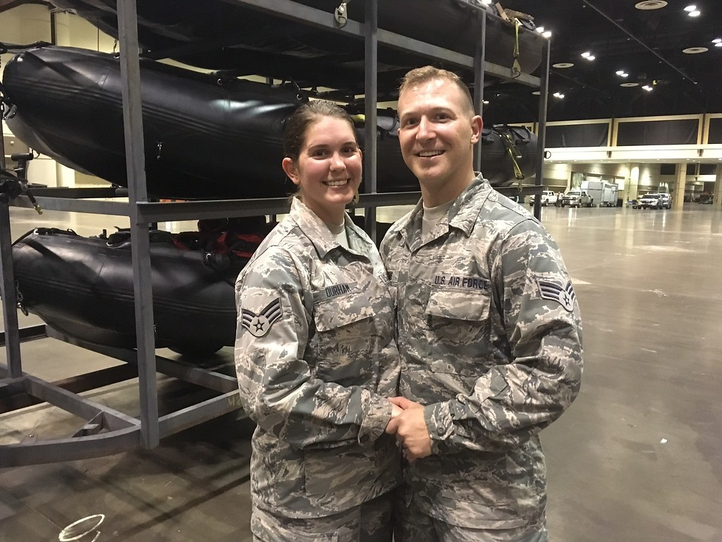. Lauren Durham, left, and Michael Davis, both members of the Air National Guard, pose at the Orange County Convention Center in Orlando, Fla., on Sunday, Sept. 10, 2017. The couple were planning to get married on a beach next weekend but were deployed to assist in the relief efforts for Hurricane Irma. Instead they got married Sunday in fatigues in a vast hangar filled with rescue vehicles and paramedics.  (AP Photo/Claire Galofaro)
