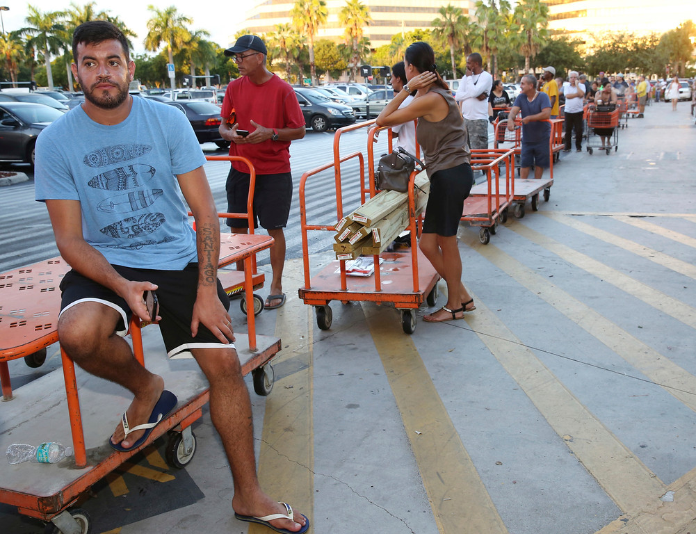 . Max Garcia, of Miami, waits in a line since dawn to purchase plywood sheets at The Home Depot store in North Miami, Fla., Wednesday, Sept. 6, 2017. Florida residents are preparing for the possible landfall of Hurricane Irma, the most powerful Atlantic Ocean hurricane in recorded history. (AP Photo/Marta Lavandier)