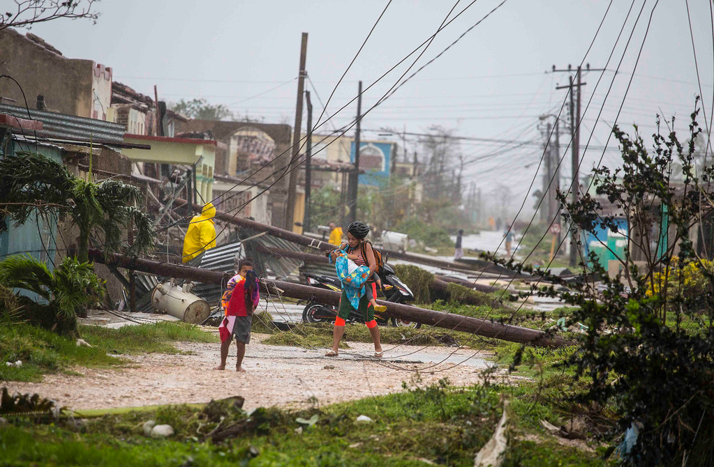 . Residents walk near downed power lines felled by Hurricane Irma, in Caibarien, Cuba, Saturday, Sept. 9, 2017. There were no reports of deaths or injuries after heavy rain and winds from Irma lashed northeastern Cuba. Seawater surged three blocks inland in Caibarien. (AP Photo/Desmond Boylan)