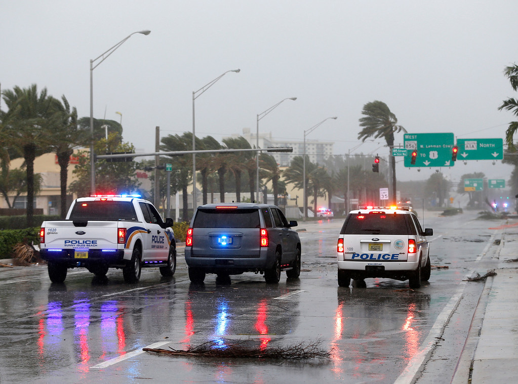 . Police cars block a road strewn with debris from roof damage caused by high winds brought on by Hurricane Irma, Saturday, Sept. 9, 2017,  in Sunny Isles Beach, Fla. (AP Photo/Wilfredo Lee)