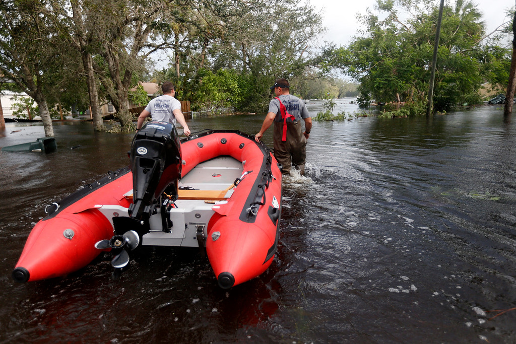 . Firefighters pull a boat into in a flooded neighborhood to check for possible rescues in the aftermath of Hurricane Irma in Bonita Springs, Fla., Monday, Sept. 11, 2017. (AP Photo/Gerald Herbert)