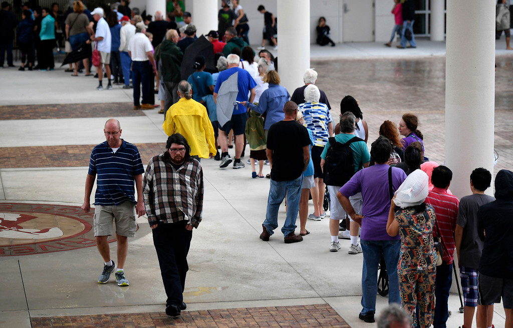. People stand in line for breakfast in the disaster shelter at Riverview High School in Sarasota, Fla. on Sunday, Sept. 10, 2017, in advance of Hurricane Irma. The full shelter is closed to new evacuees. (Mike Lang/Sarasota Herald-Tribune via AP)