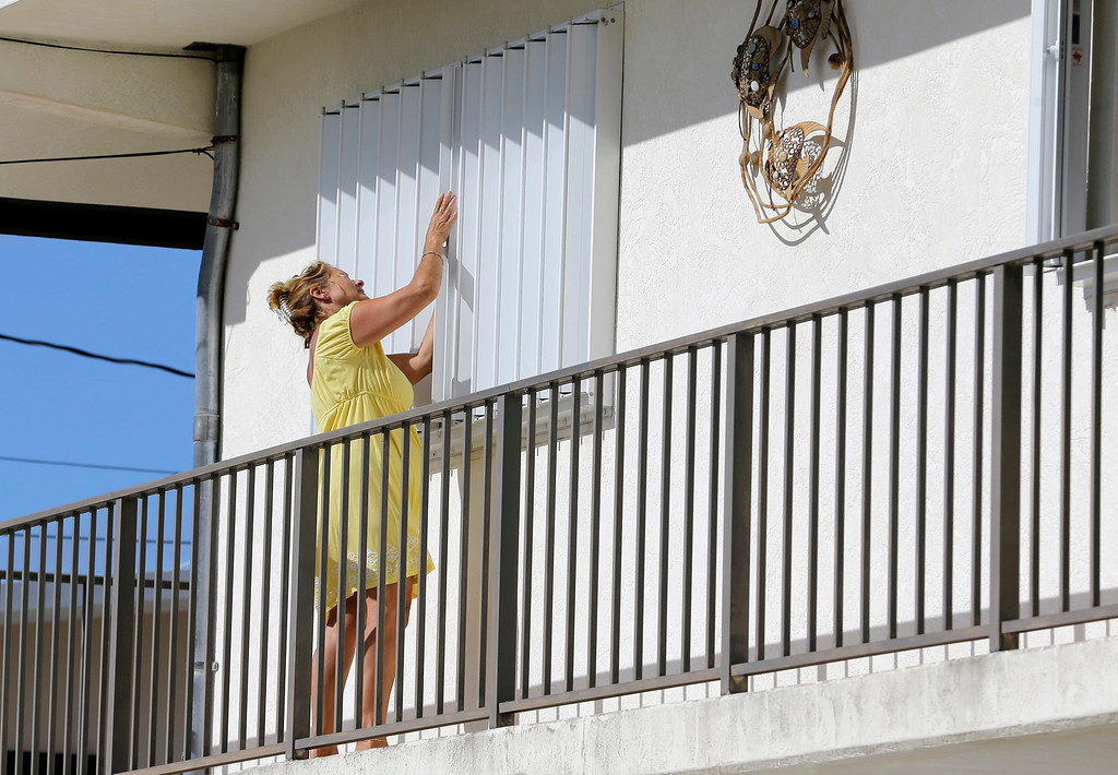 . Nancy Eaves works on her hurricane shutter at her home as he prepares for Hurricane Irma, Wednesday, Sept. 6, 2017, in Key Largo, Fla. Hurricane Irma roared into the Caribbean with record-setting force early Wednesday, shaking people in their homes on the islands of Antigua and Barbuda on a path toward Puerto Rico and possibly Florida by the weekend. (AP Photo/Alan Diaz)