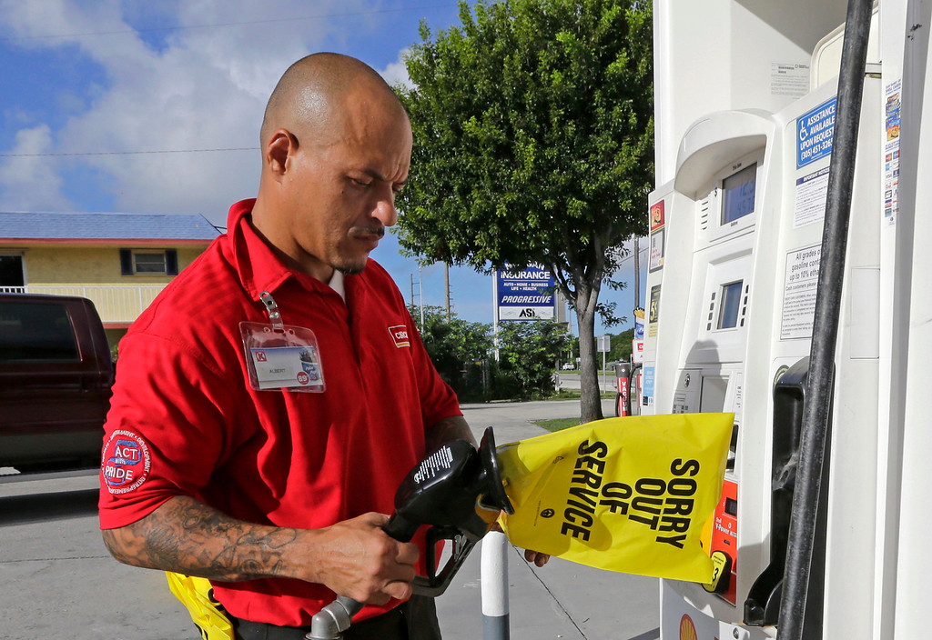 . Gas station employee Albert Fernandez covers a pump after running out of gas as the demand for gas has increased due to Hurricane Irma, Wednesday, Sept. 6, 2017, in Key Largo, Fla.  Irma roared into the Caribbean with record force early Wednesday, its winds shaking homes and flooding buildings on a chain of small islands along a path toward Puerto Rico, the Dominican Republic, Haiti, Cuba and likely Florida by the weekend. (AP Photo/Alan Diaz)