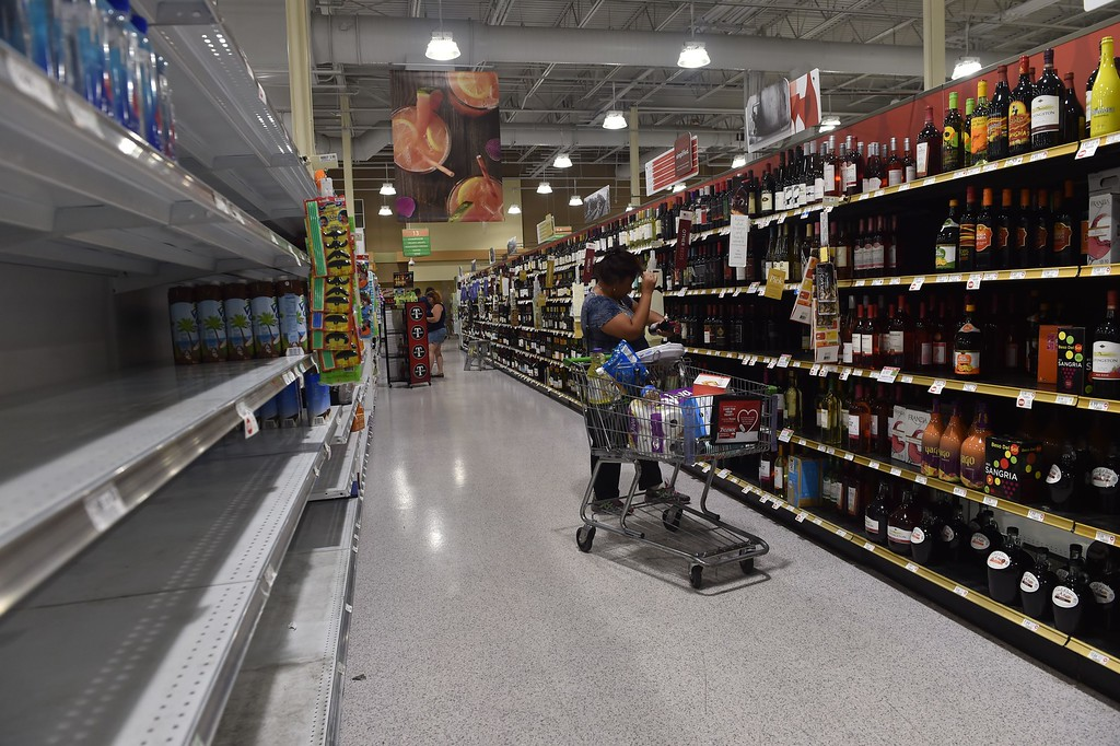 . A woman buys wine across from the empty water shelf in a supermarket in Riverview, Florida on September 9, 2017. Hurricane Irma weakened slightly to a Category 4 storm early Saturday, according to the US National Hurricane Center, after making landfall hours earlier in Cuba with maximum-strength Category 5 winds. (NICHOLAS KAMM/AFP/Getty Images)