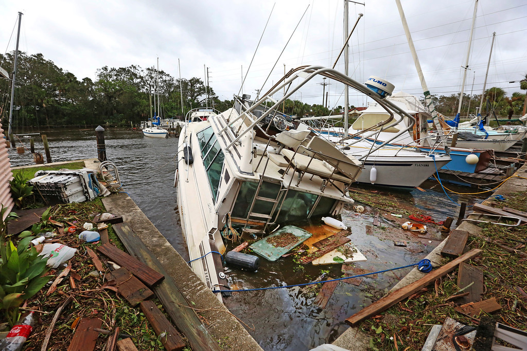. A sinking boat is surrounded by debris in the aftermath of Hurricane Irma at Sundance Marine in Palm Shores, Fla., Monday, Sept. 11, 2017 (Red Huber/Orlando Sentinel via AP)
