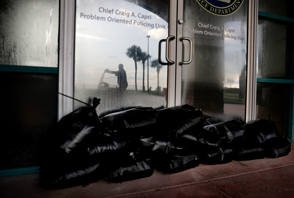 . Sandbags sit outside a police station office as a worker secures the grounds of a hotel along the beach ahead of Hurricane Irma in Daytona Beach, Fla., Friday, Sept. 8, 2017. Coastal residents around South Florida have been ordered to evacuate as the killer storm closes in on the peninsula for what could be a catastrophic blow this weekend. (AP Photo/David Goldman)